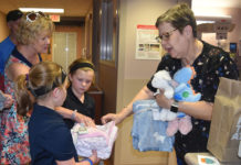 Pauline Hayes, right, NICU manager, accepts blankets and stuffed animals from Madelyn and Shelby Medley on behalf of the UofL Center for Women & Infants.